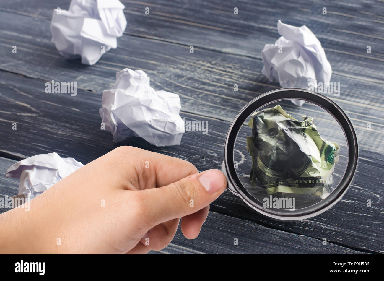 A crumpled dollar on a table next to white paper balls. The process of thinking and finding new business ideas, profitable solutions. Attraction of in - Stock Image