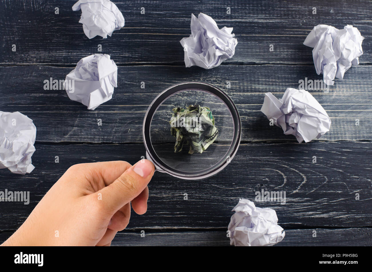 Crumpled dollar among white paper balls on a dark background. The concept of a good idea, brainstorming, a successful solution and a search of differe - Stock Image