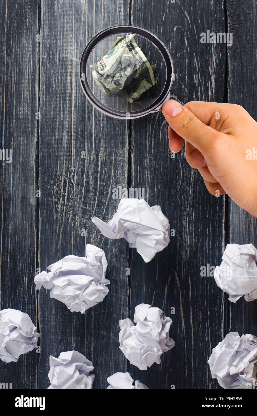 Crumpled dollar on top of white paper balls on a dark background. The best idea, the process of thinking about new business solutions, the investment  - Stock Image