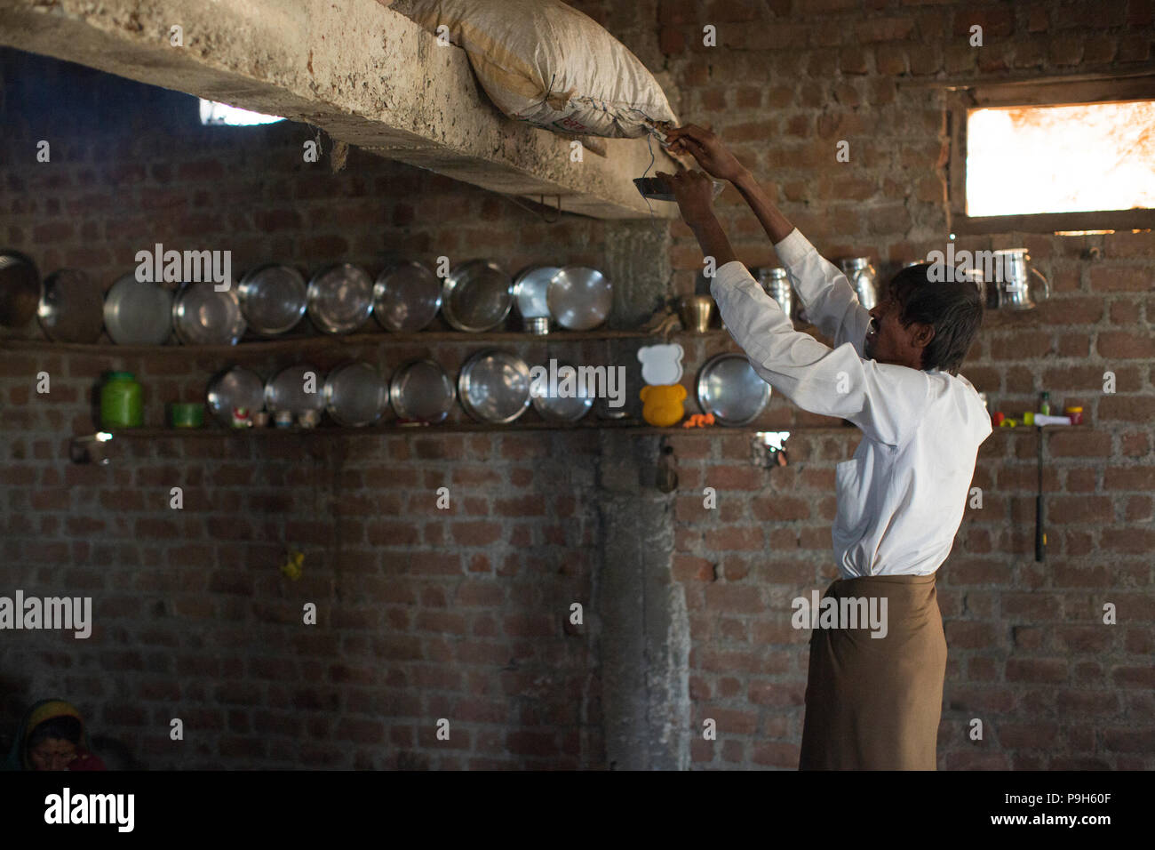 A man filling a bowl with groundnuts from a sack stored in the rafters of his kitchen, India. - Stock Image