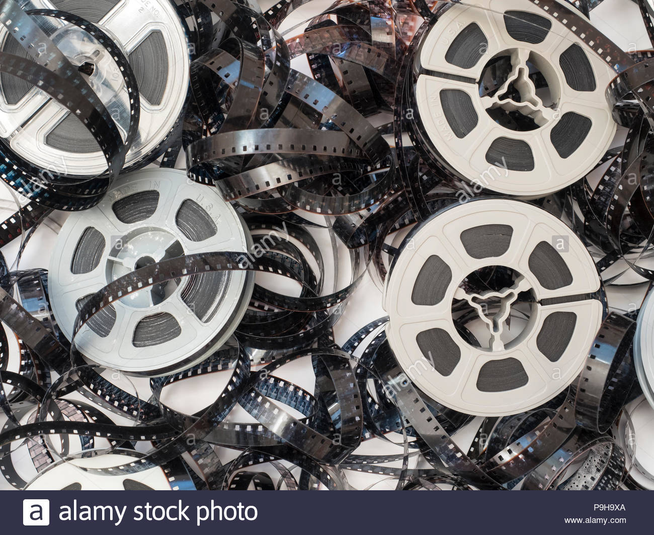 Overhead view of a pile of discarded, more than 50-year old and faded 8 millimeter movie film with equally old and dirty, dusty plastic film reels, wh - Stock Image