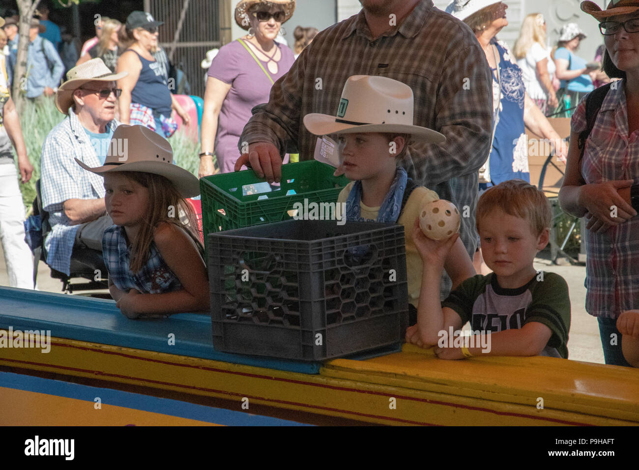Kids playing ball toss at the Calgary Stampede Midway, Stampede Grounds, Calgary, Alberta, Canada - Stock Image