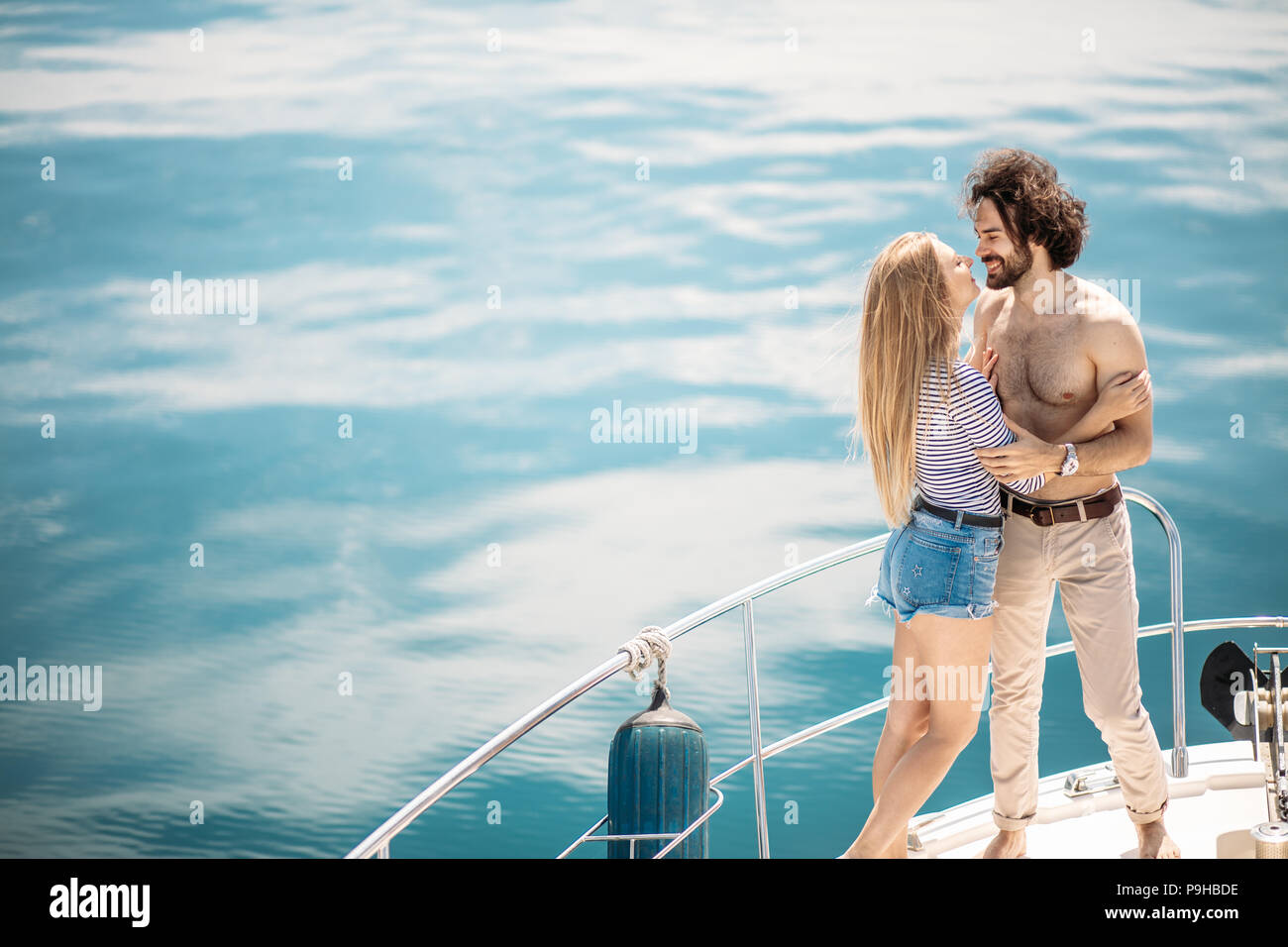 Passionate loving caucasian couple dancing on bow of sailboat, over blue sea background with copyspace. Summer vacation, People Relations and Love, Ro Stock Photo