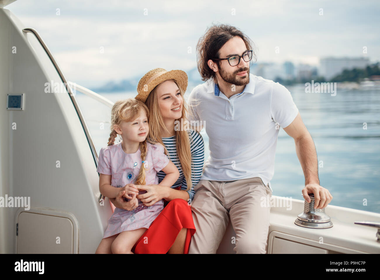 Cute married couple with adorable little daughter looking happy while enjoying romantic trip on the holydays, sailing on sea boat, spending nice time  - Stock Image