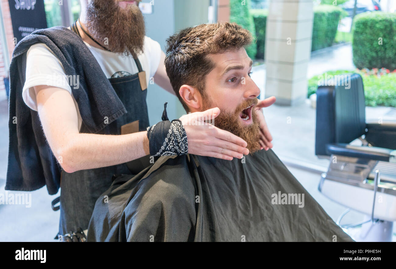 Redhead bearded young man making a funny face before a change of look - Stock Image