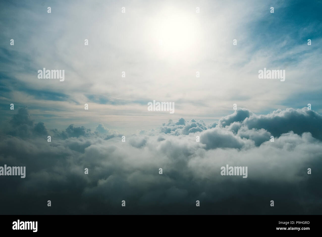 a view from high above the clouds. View of the clouds from the window of the aircraft. Non-flying weather. The sun shines through the dark blue and gr - Stock Image