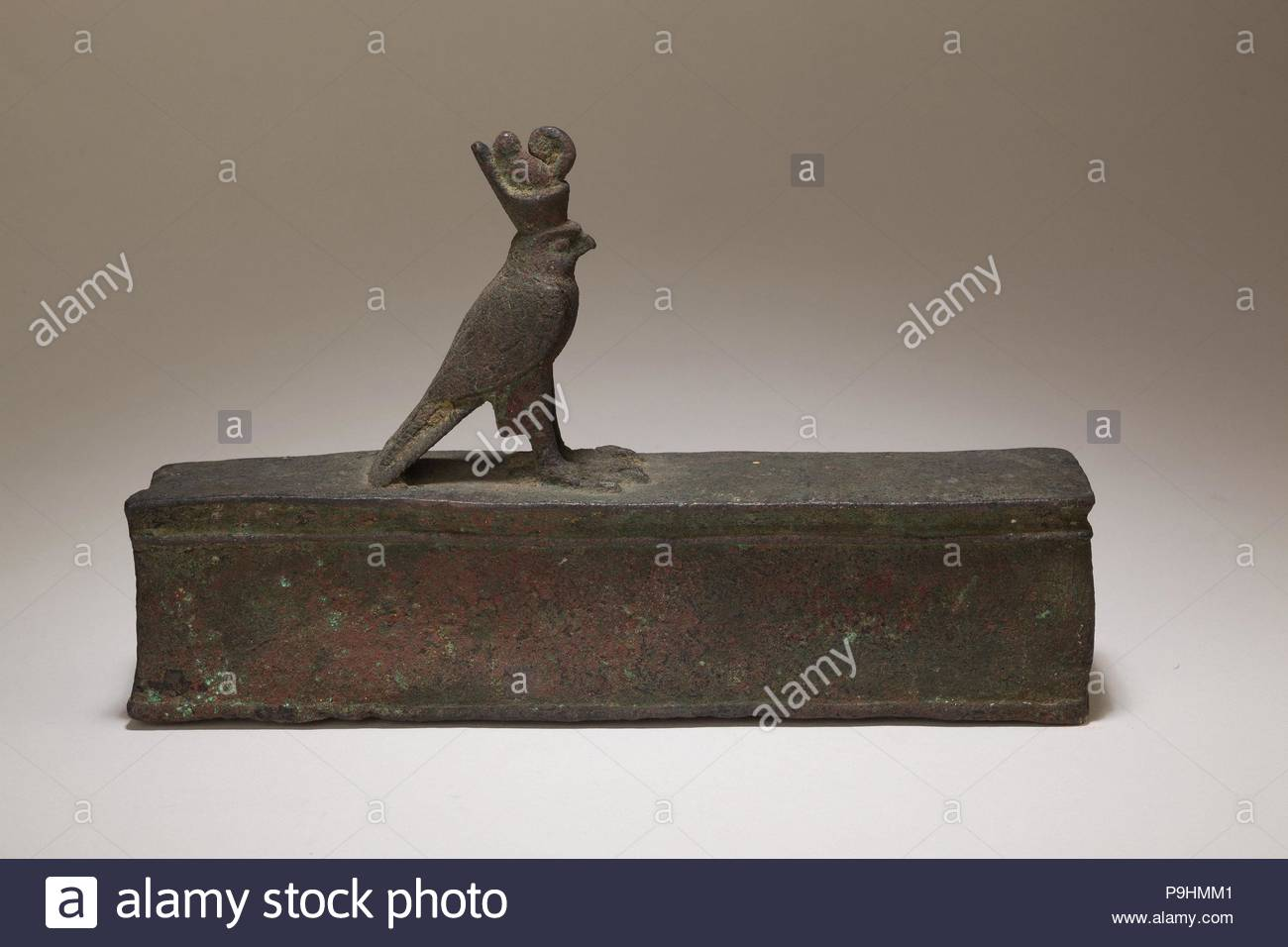 Case for an animal mummy topped by a falcon, Late Period–Ptolemaic Period, 664–30 B.C., From Egypt, Cupreous metal, H. 13.4 cm (5 1/4 in.); W. 4.9 cm (1 15/16 in.); L. 21.2 cm (8 3/8 in.), The falcon god Horus stands with his wings swept back. He has a prominent beak, large rounded eyes, and a strong brow, which supports the double crown of Egypt. This royal crown symbolizes the union of Lower and Upper Egypt, and highlights Horus' role as the legitimate ruler of the entire land. - Stock Image