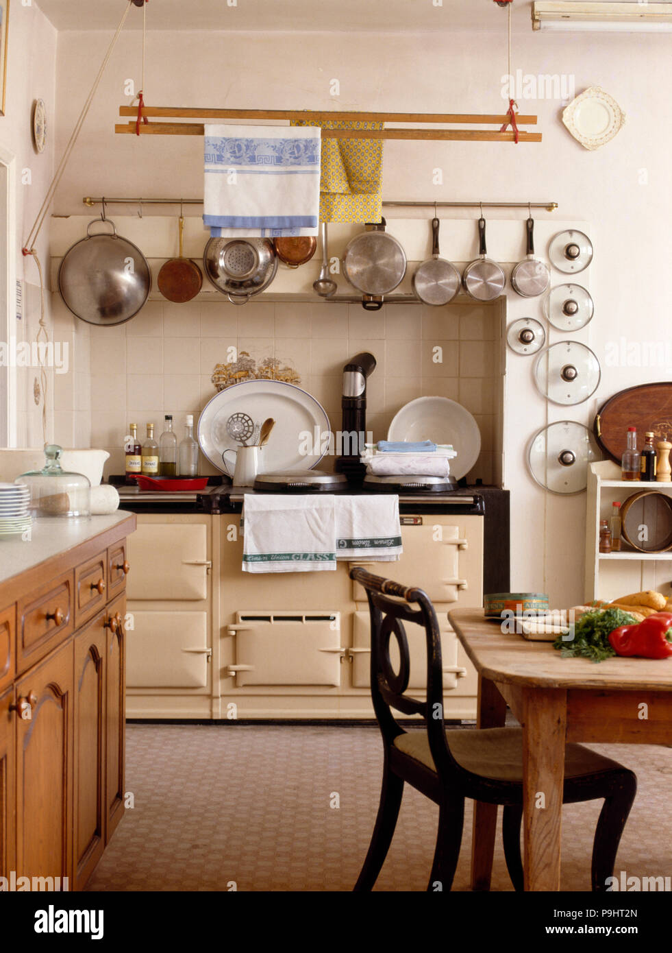 Stainless Steel Pans On Rack Above Cream Aga In A Country Kitchen