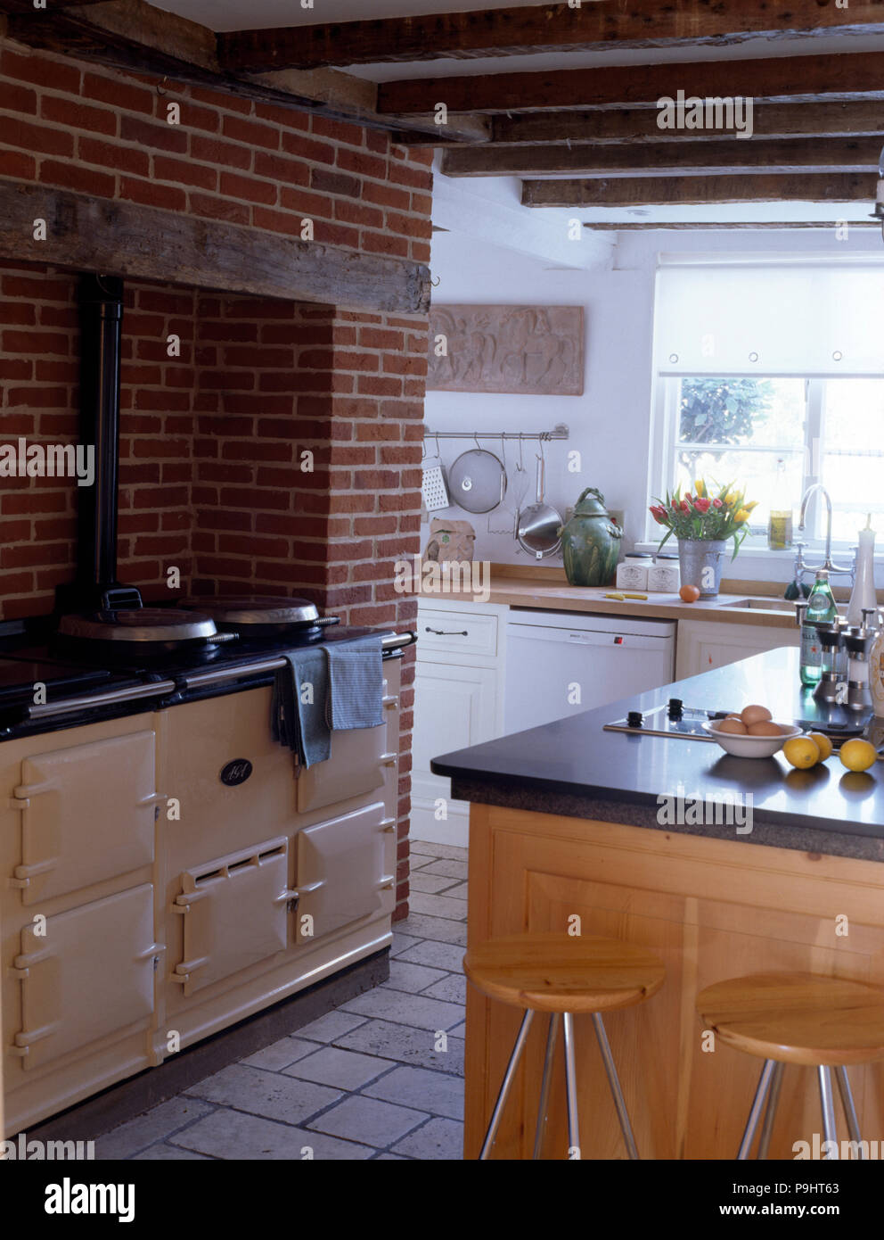 Cream aga in a country kitchen with an exposed brick wall and rustic wooden ceiling beams
