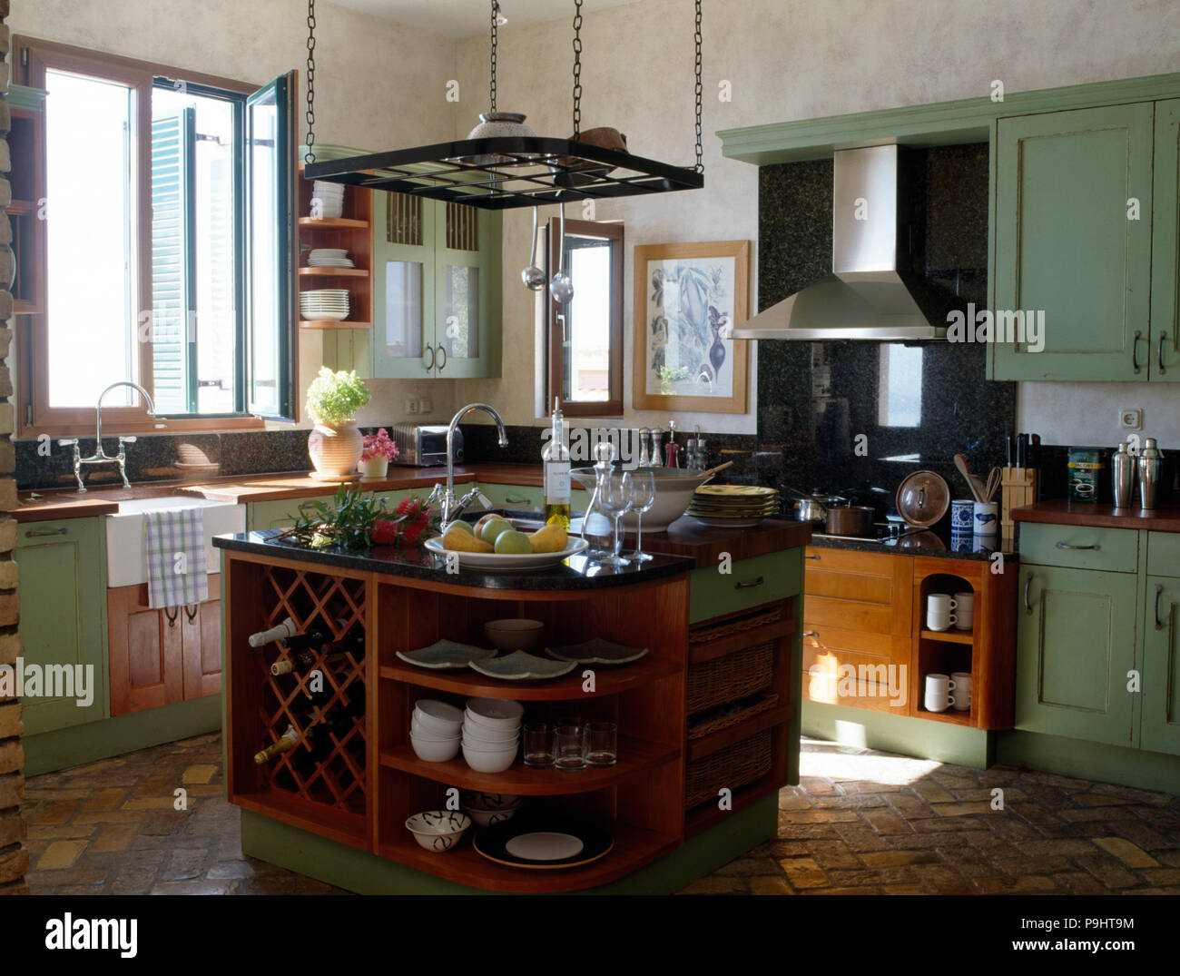 Hanging Rack Above Island Unit With An Integral Wine Rack In A Coastal Kitchen With Green Doors On Fitted Cupboards Stock Photo Alamy