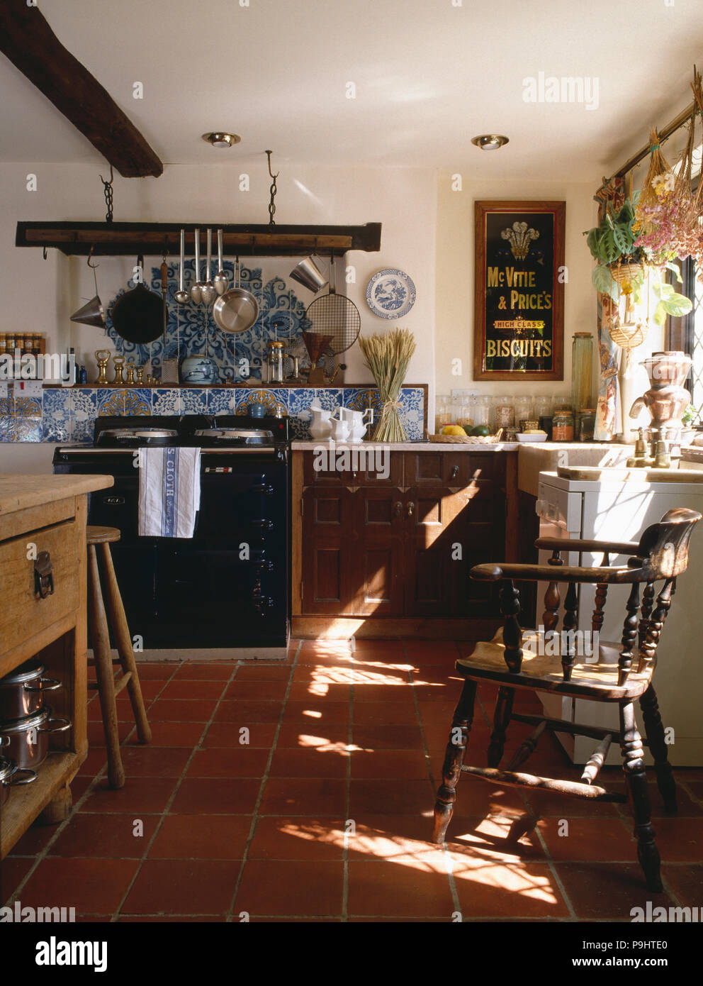 Black Aga Below Blue And White Tiles In Country Kitchen With Terracotta Floor Tiles Vintage Mcvitie Biscuit Sign Stock Photo Alamy