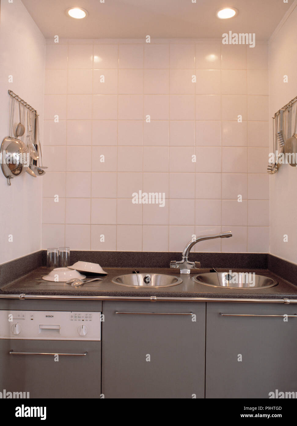 White Wall Tiles Above Double Circular Steel Sinks In Grey Kitchen Unit With Built In Dishwasher Stock Photo Alamy