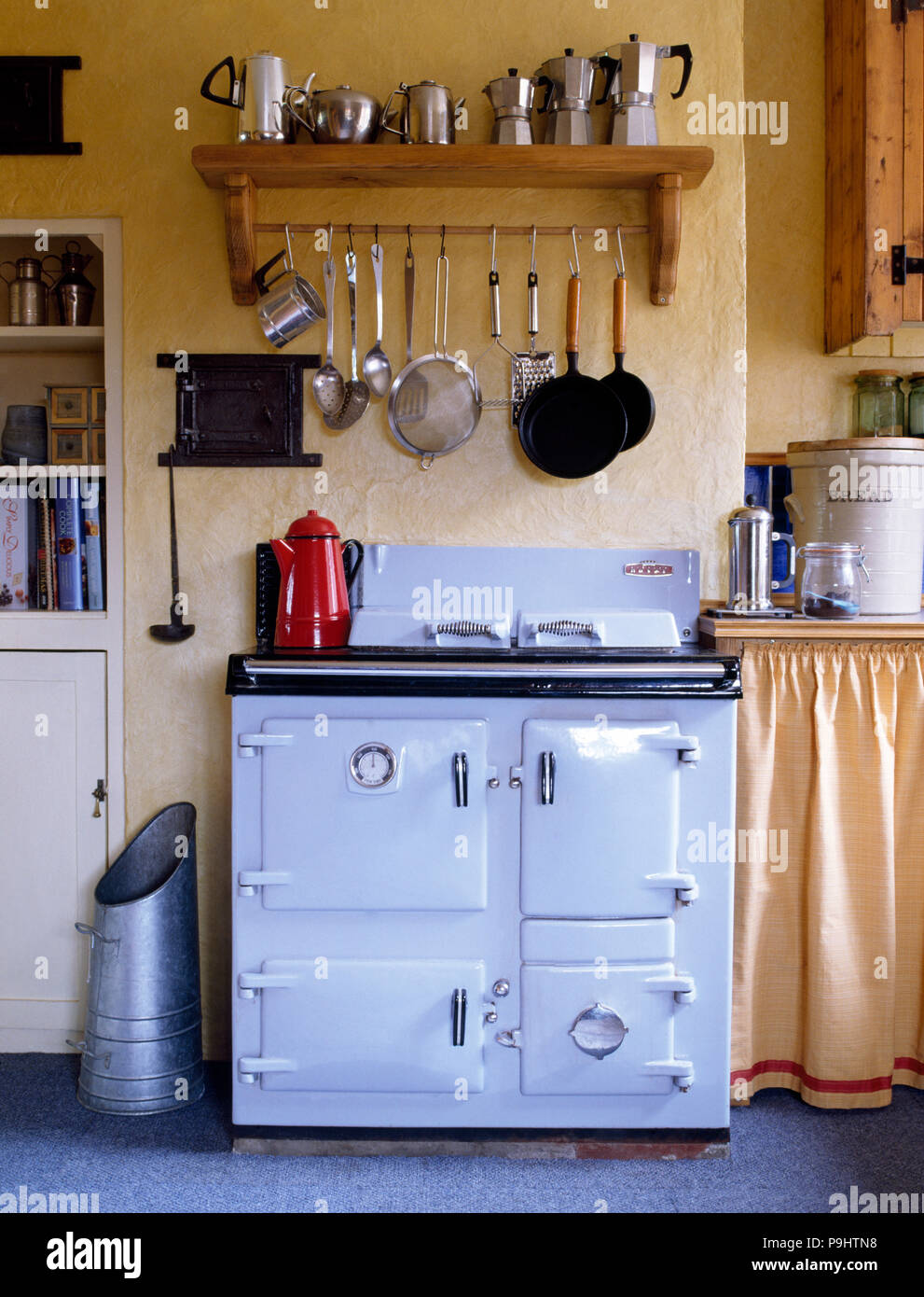 White Aga oven below a pine shelf with a row of Moka coffee pots   in a cottage kitchen with a galvanized zinc coal hod - Stock Image