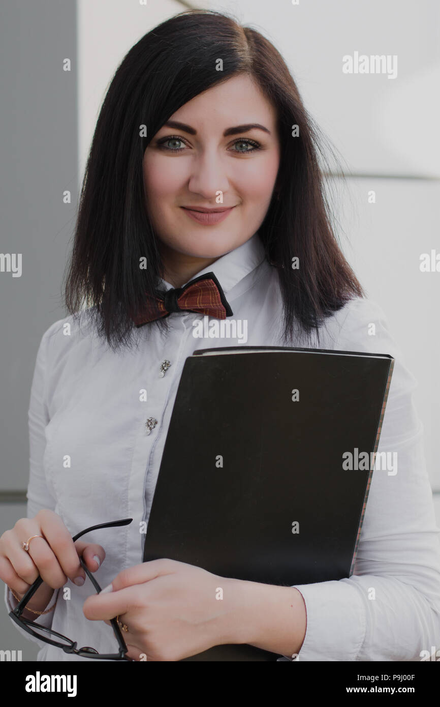 Modern business, woman near the office ponders business plan - Stock Image