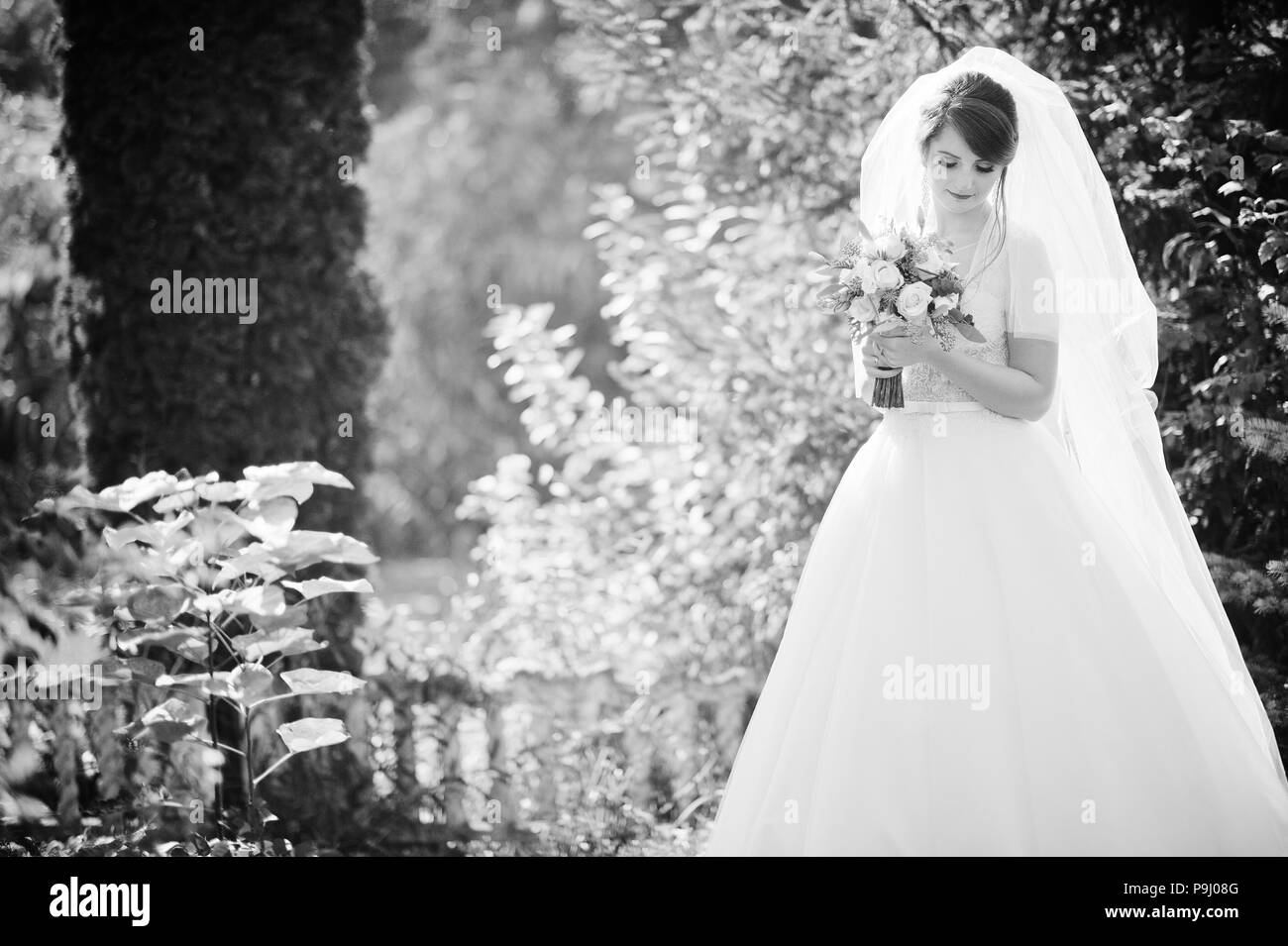 Portrait of a gentle gorgeous bride holding lovely wedding bouquet in her hands outdoors. - Stock Image