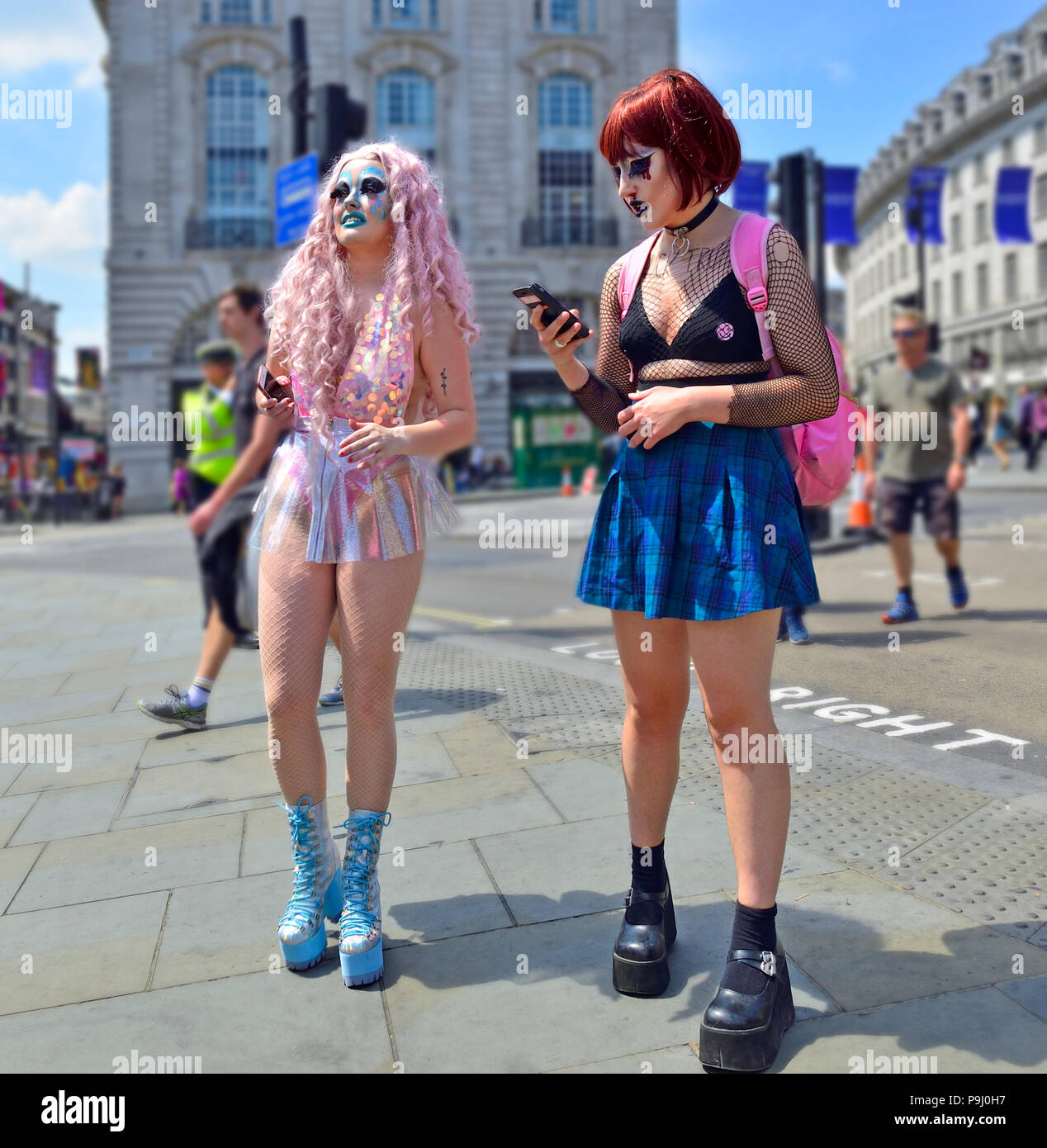 Two heavily-made up and interestingly-dressed girls in Piccadilly Circus, London, England, UK. Heading for an Anti-Trump march during the president's  - Stock Image