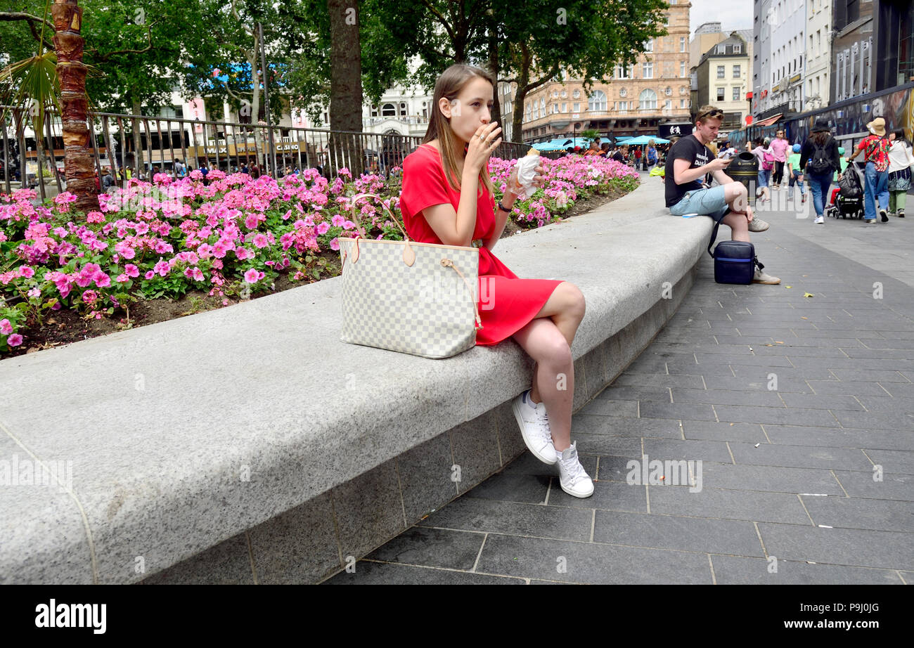 Young woman in a red dress sitting in Leicester Square eating her lunch, London, England, UK. - Stock Image