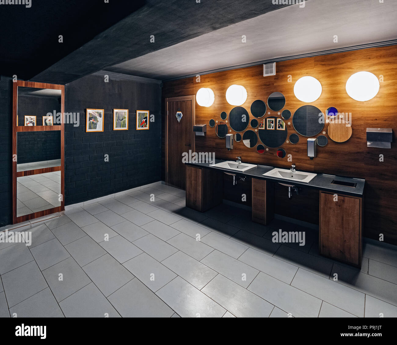 Modern restaurant restroom with wooden decoration and black painted ...