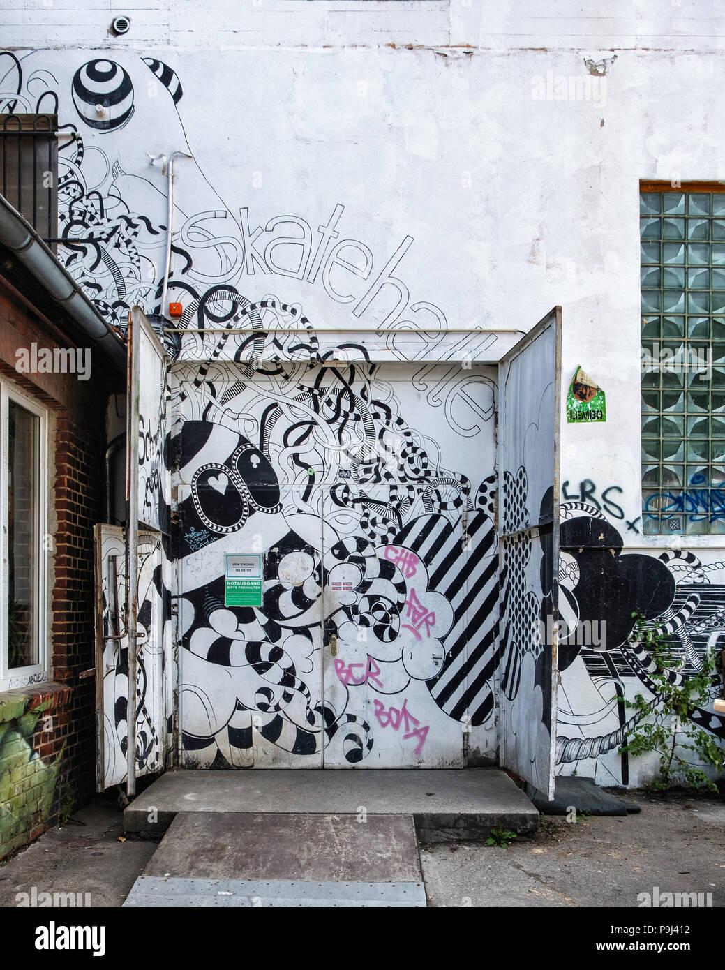 Berlin, Friedrichshain, RAW Gelände. Skatehalle skate boarding hall emergency exit with black & white artwork - Stock Image
