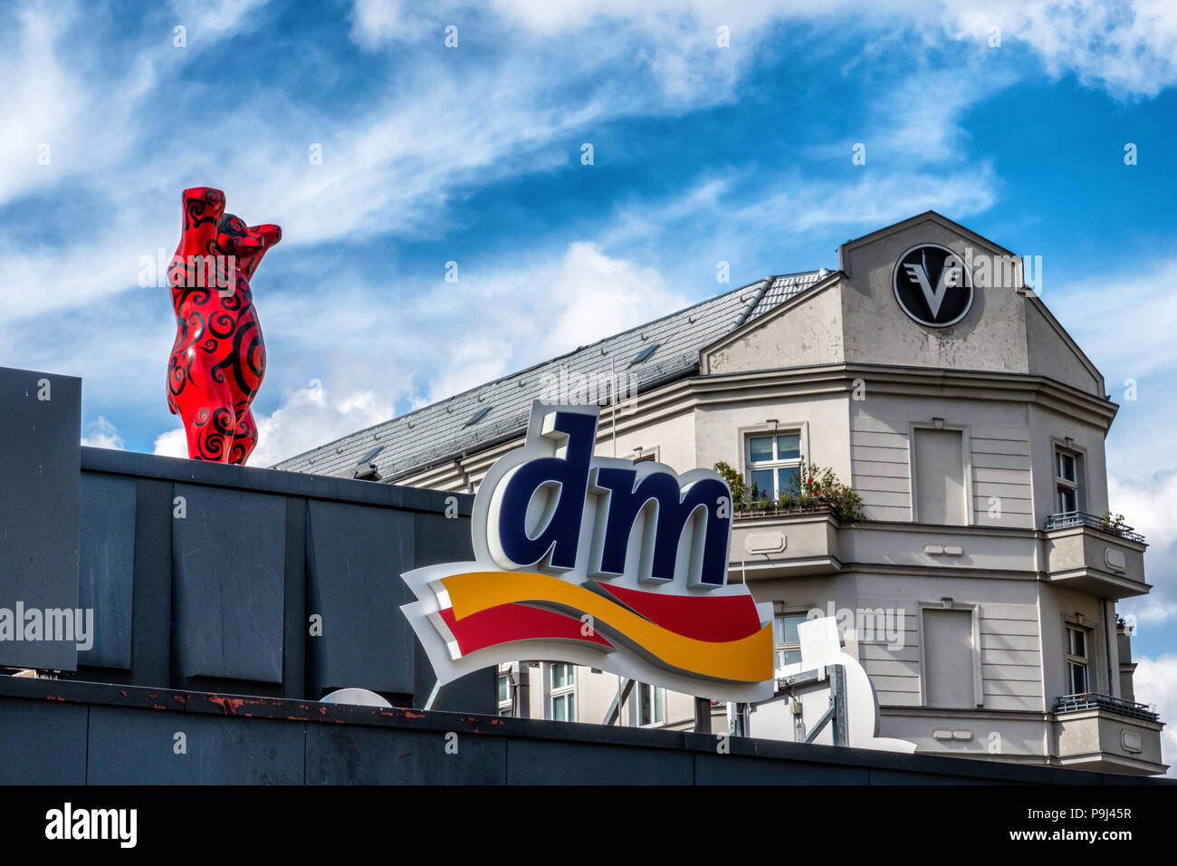 Berlin, Friedrichshain, Red Berlin Buddy bear, DM drugstore logo and apartment buildings - Stock Image