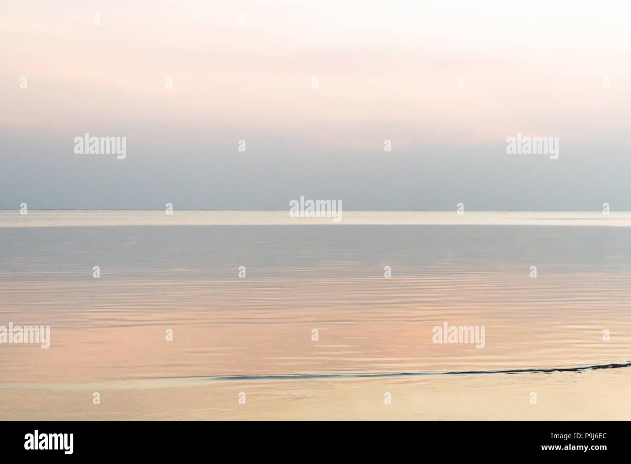 A minimalist landscape with a skyline covered with a single line of a smoking water. Place, where a river meets the sea, Latvia - Stock Image