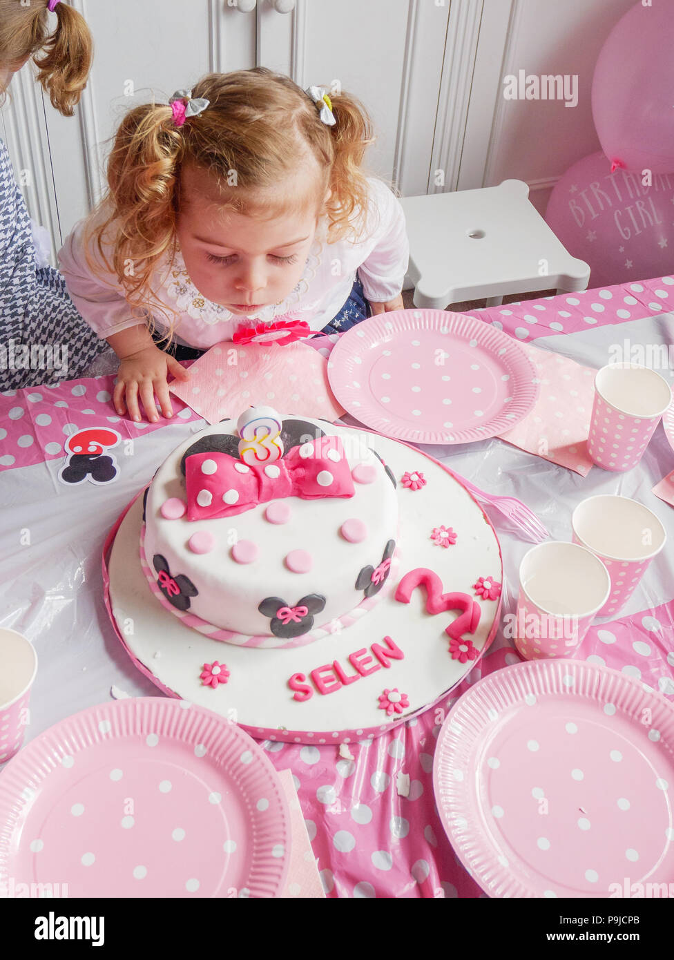 Three Year Old Girl Blowing Out Candles On Her Birthday Cake UK