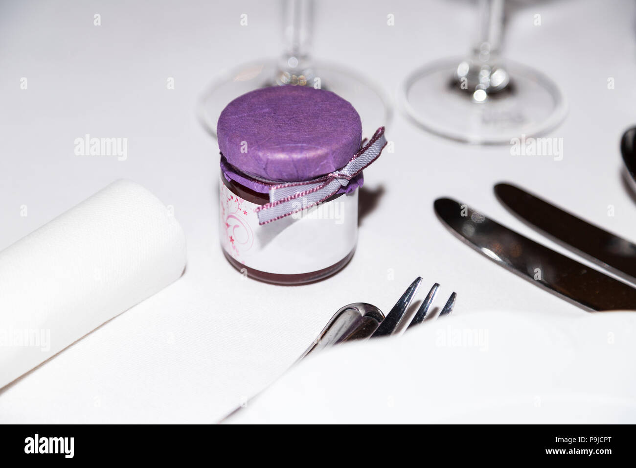 Jar of decorated confiture standing at wedding party table close-up - Stock Image