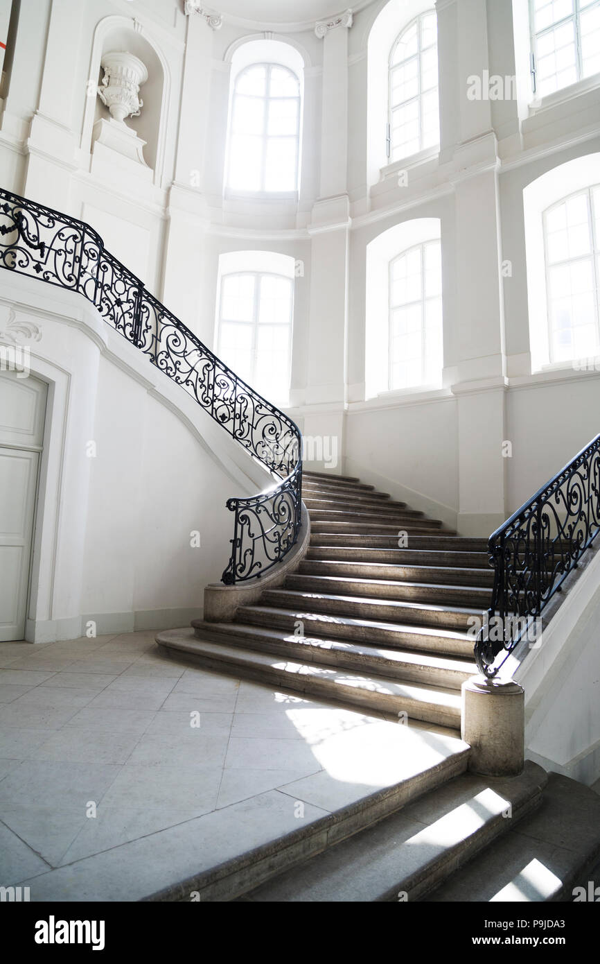 Big staircase with openwork metal curved banister inside - Stock Image