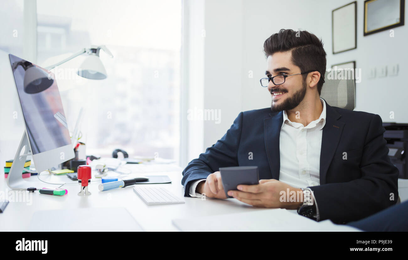 Businessman analyzing investment charts with calculator on office desk - Stock Image