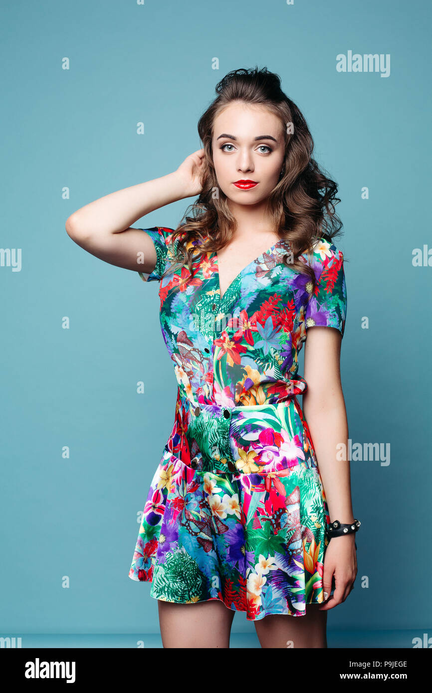 4ca060e82 Pretty lovely girl with wavy hair in beautiful floral dress posing over  blue background.