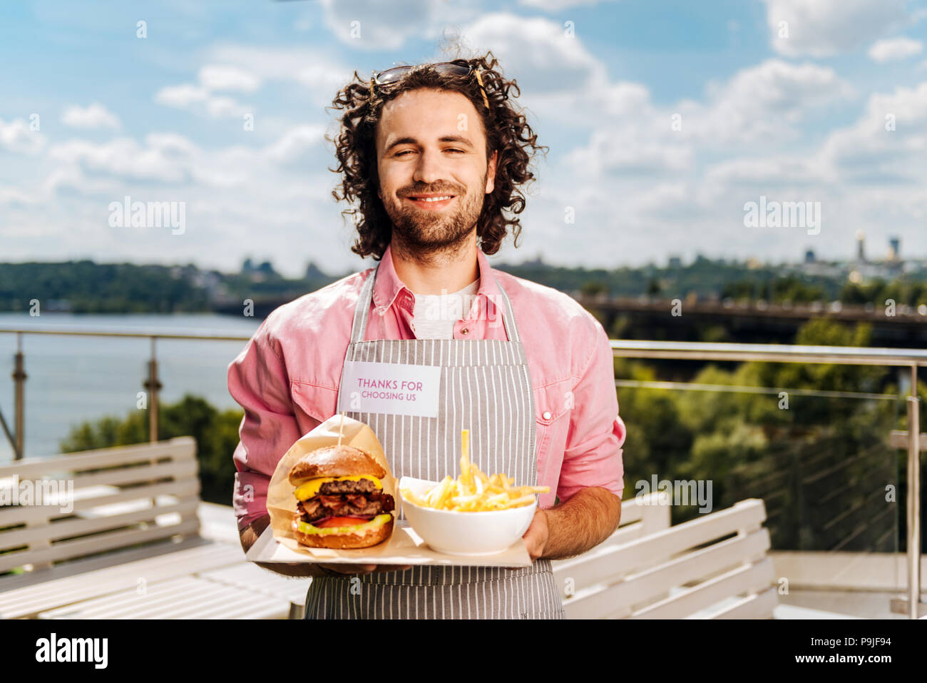 Fast food worker bringing burger with fries for his clients - Stock Image