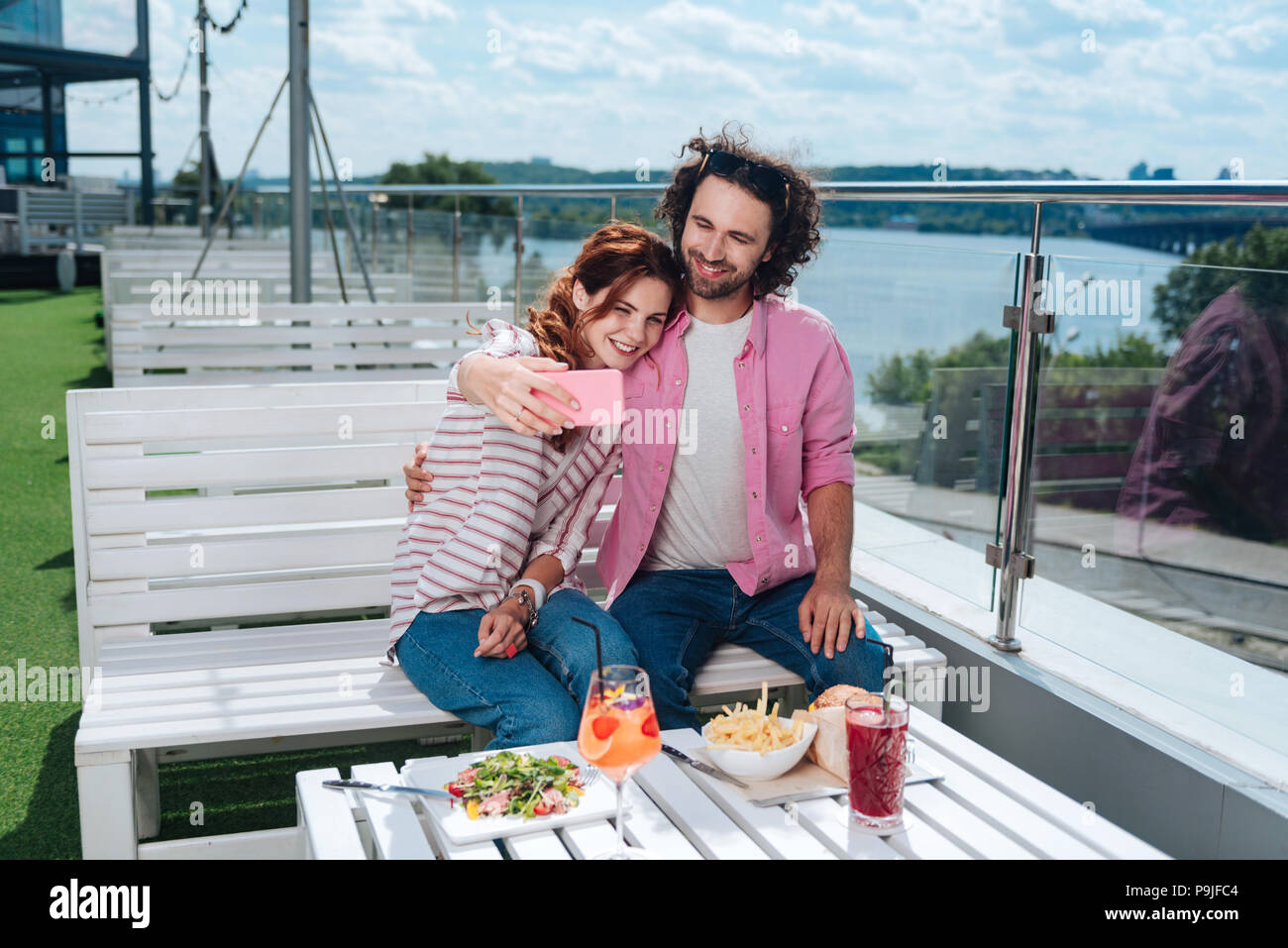 Beaming woman making selfie with her boyfriend - Stock Image