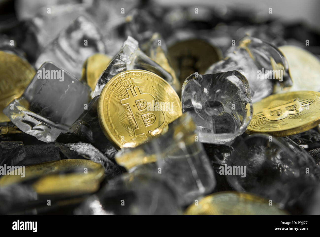 Golded bitcoins on ice background. The concept of the exchange in winter. Freeze. Blockchain mining. Digital money and virtual cryptocurrency concept. Iinvestment. Bussiness, commercial. - Stock Image