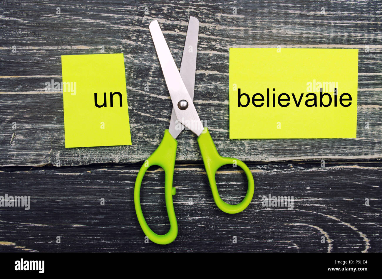 "scissors cut the word unbelievable. concept believable. cuts the word ""un. ""I can, goal achievement, potential, overcoming Stock Photo"