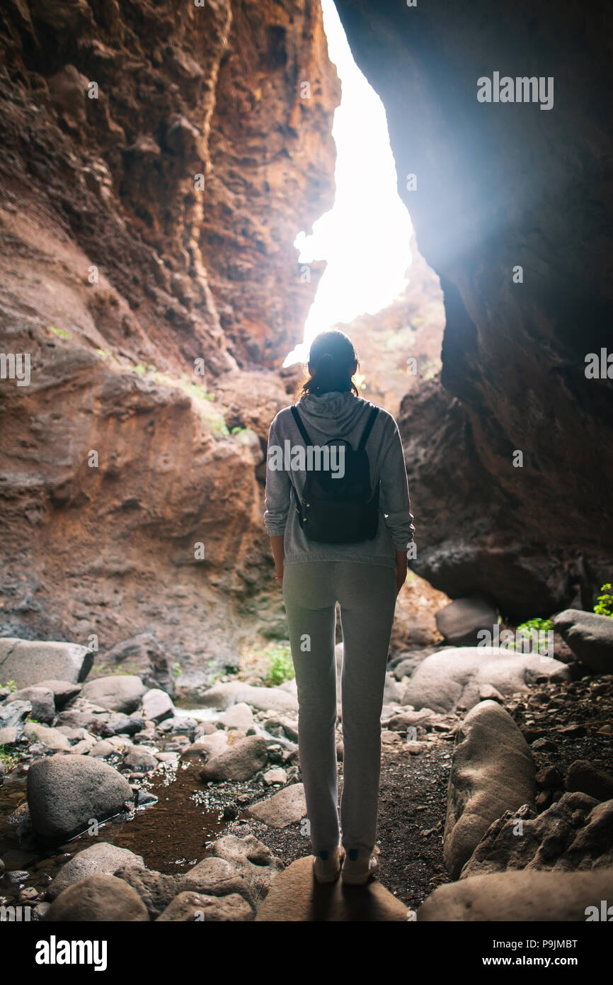 Silhouette of traveler woman in mountain cave. Light at the end of cave - Stock Image