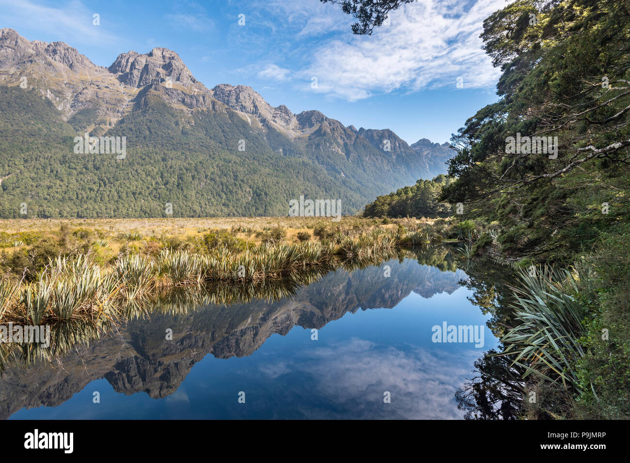 Mirror Lake with water reflections of the mountains, Fiordland National Park, Milford Highway, Southland, New Zealand Stock Photo