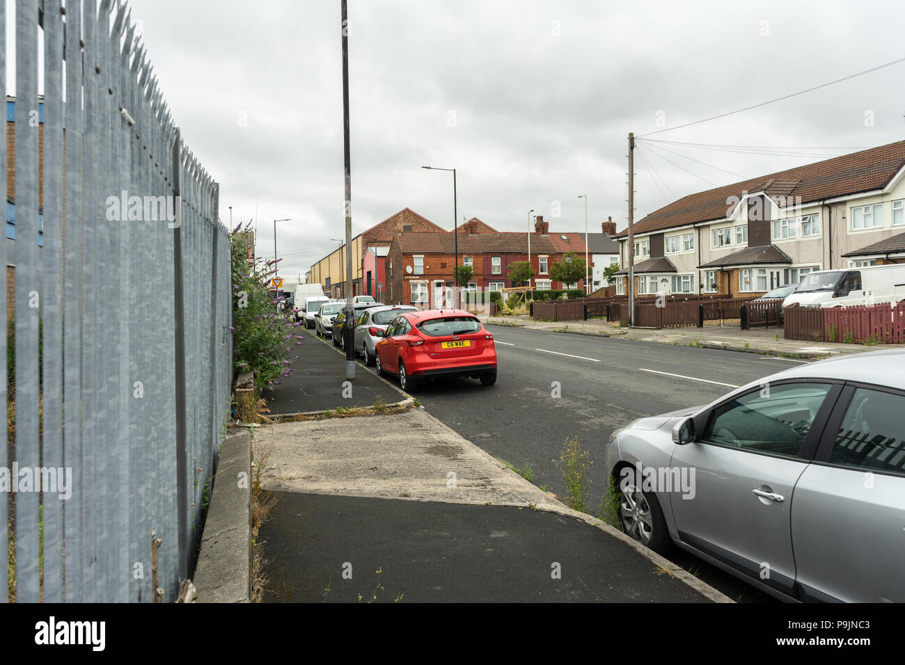 Street view of council houses in Birkenhead, Wirral, UK, Street scene with cars and industrial estate - Stock Image
