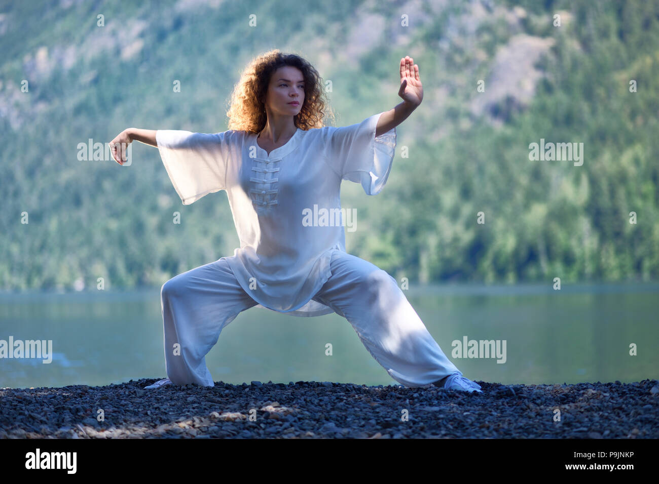 Young woman in white outfit practicing a Tai Chi, Taiji, Ban Ma Bu stance by the lake in the nature - Stock Image
