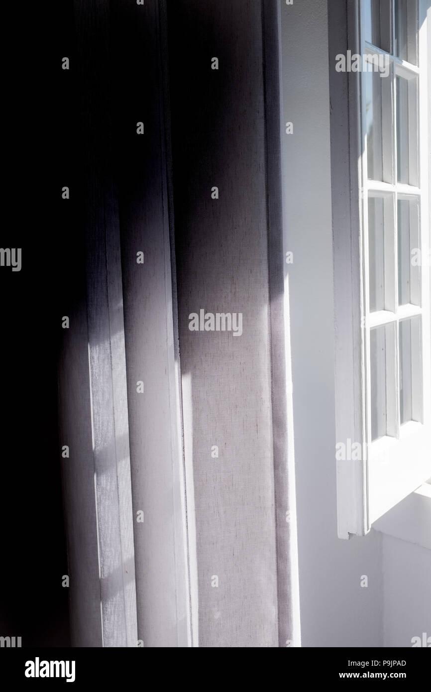Bright sunlight streaming through window - Stock Image