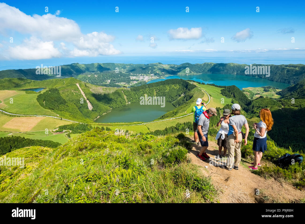 Tourists at a viewpoint over Sete Cidades, two lakes and a village in the dormant crater of a volcano on the island of Sao Miguel, The Azores - Stock Image