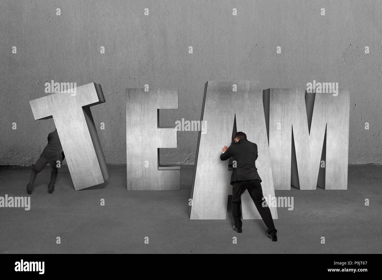 Two men moving TEAM concrete words together - Stock Image