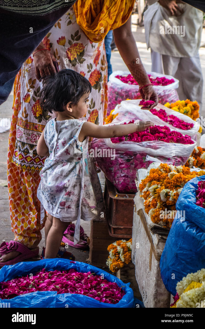 Cute little Indian girl with a woman looking at flowers in a stall in Old Delhi, India Stock Photo