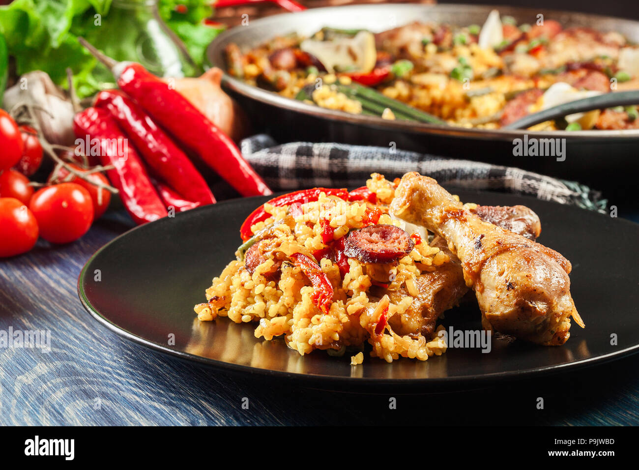 Traditional paella with chicken legs, sausage chorizo and vegetables served on black plate. Spanish cuisine Stock Photo