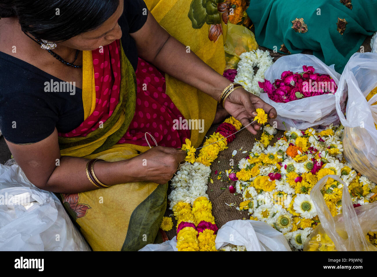 Indian woman making traditional flower garlands at a market stall in Old Delhi, Delhi, India Stock Photo