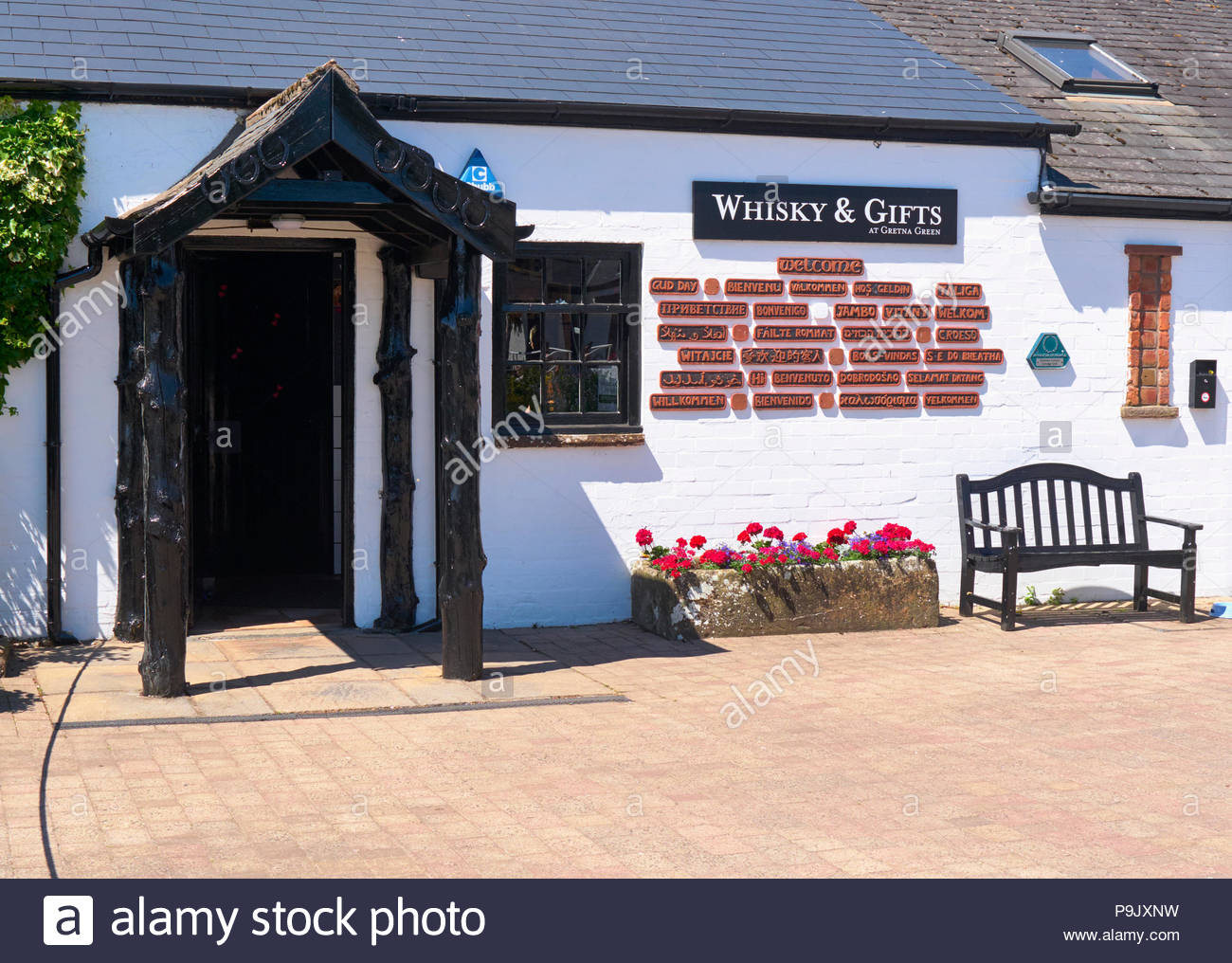 The whiskey and gift shop with welcome sign in many languages in gretna green in - Stock Image