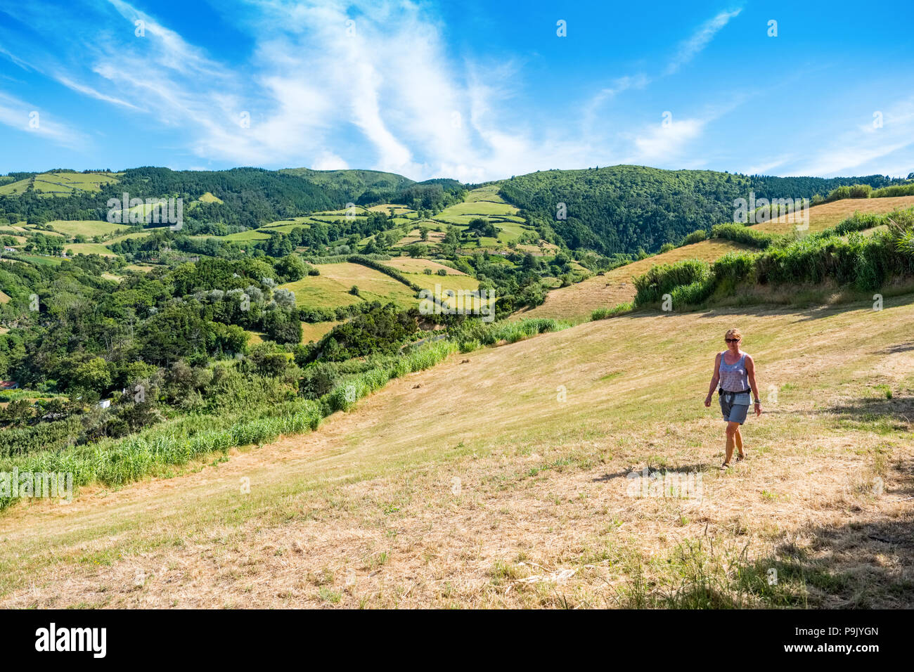 Female walking on the north coast of Sao Miguel, The Azores - Stock Image