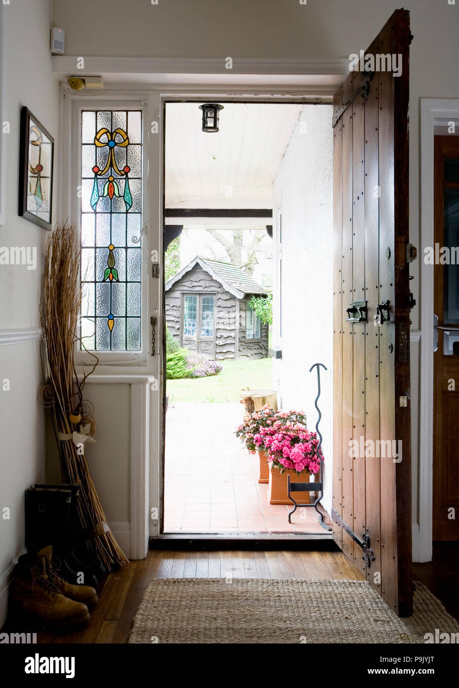 Stained Glass Window Beside Open Oak Front Door In Small Hall Stock