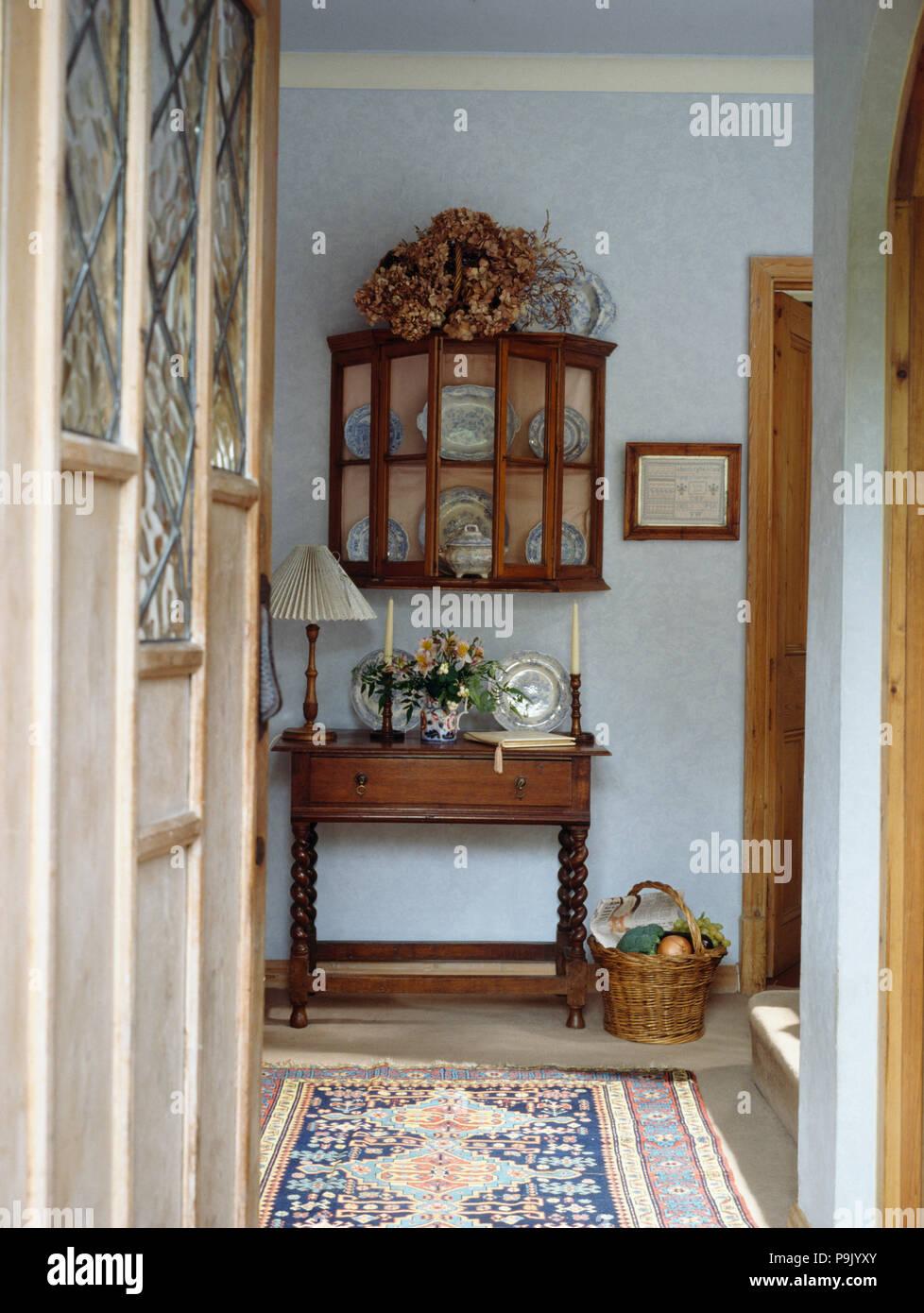 Door open to small blue hall with antique cupboard with glazed doors above  table - Door Open To Small Blue Hall With Antique Cupboard With Glazed Doors