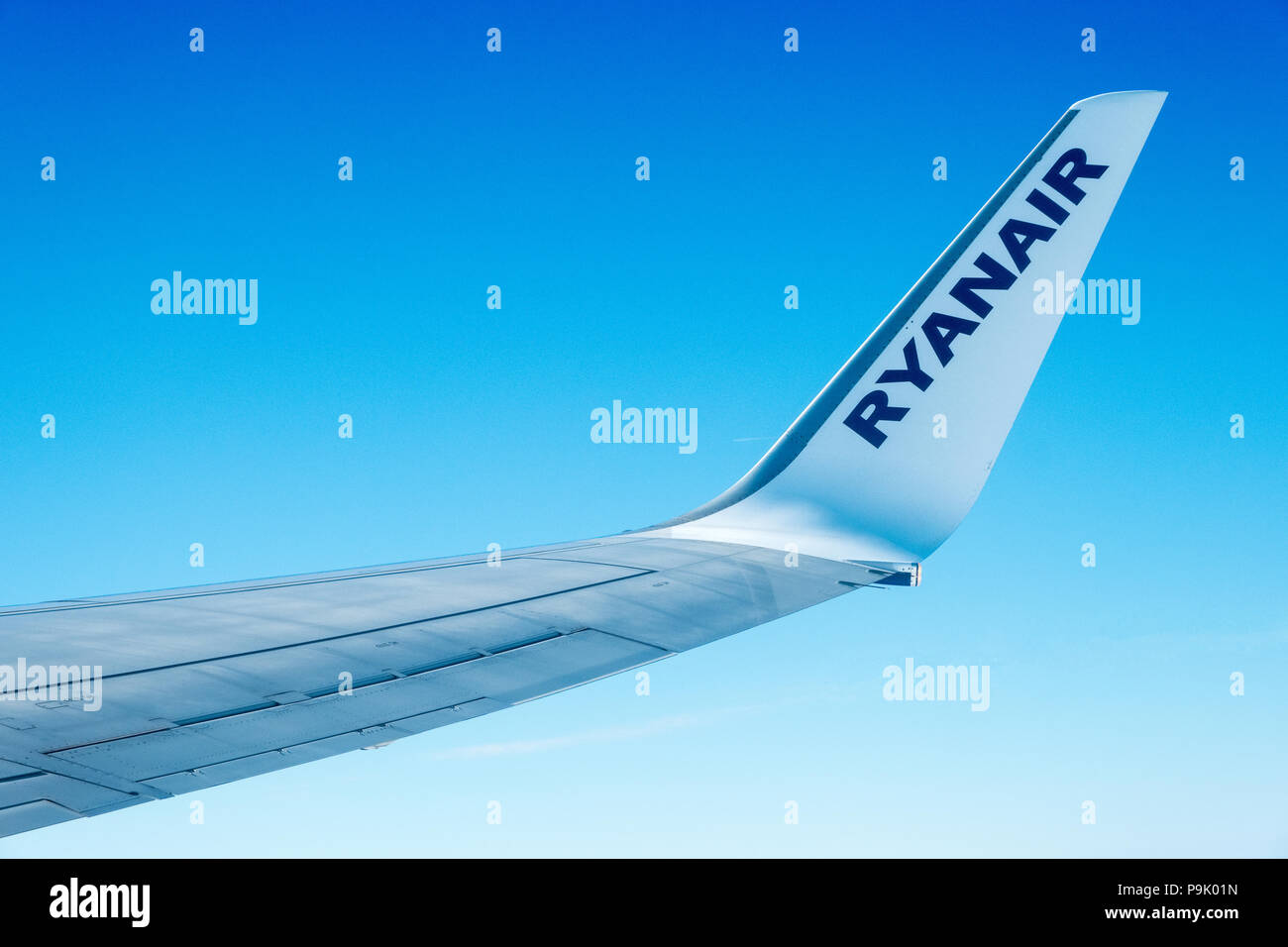 Ryanair airplane wing and blue skies - Stock Image