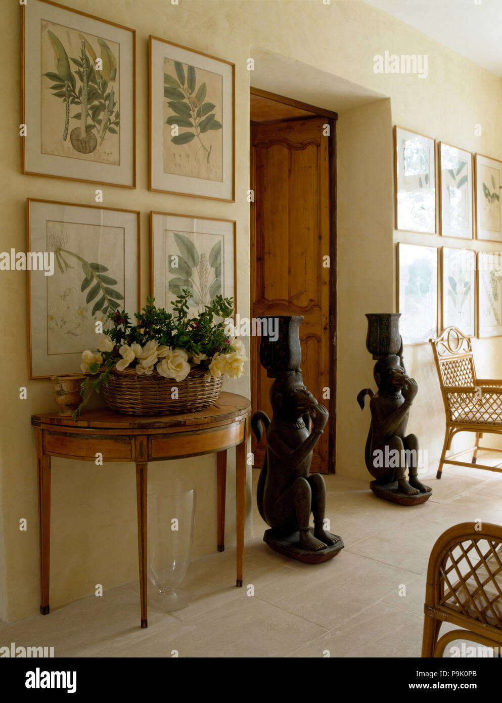 Ordinaire Framed Botanical Prints Above Console Table With A Floral Arrangement In A  Basket In A Cream Hall With Tall Oriental Statues